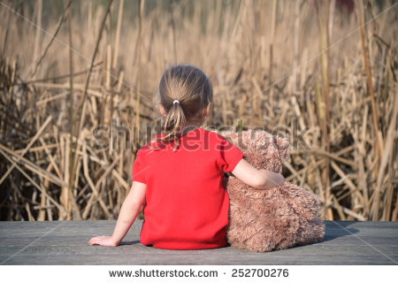 stock-photo-girl-in-red-dress-sitting-on-a-wooden-board-with-teddy-bear-looking-at-field-of-yellow-grass-252700276